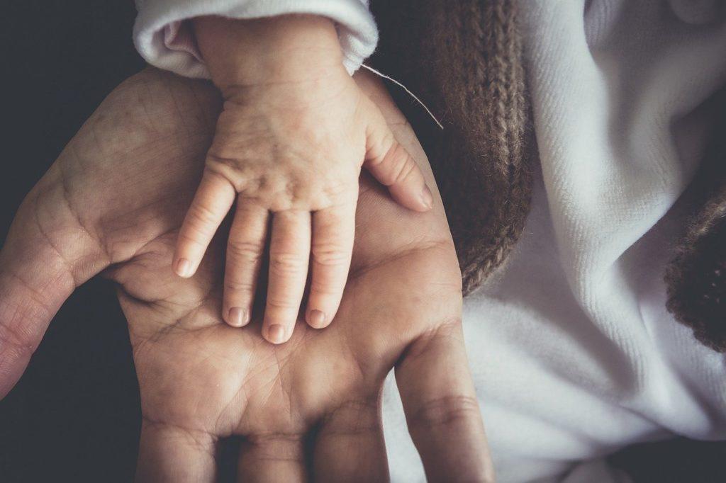 sophro-analyse, adulte et enfant intérieur travaillent main dans la main. Main de bébé dans la main ouverte d'un adulte